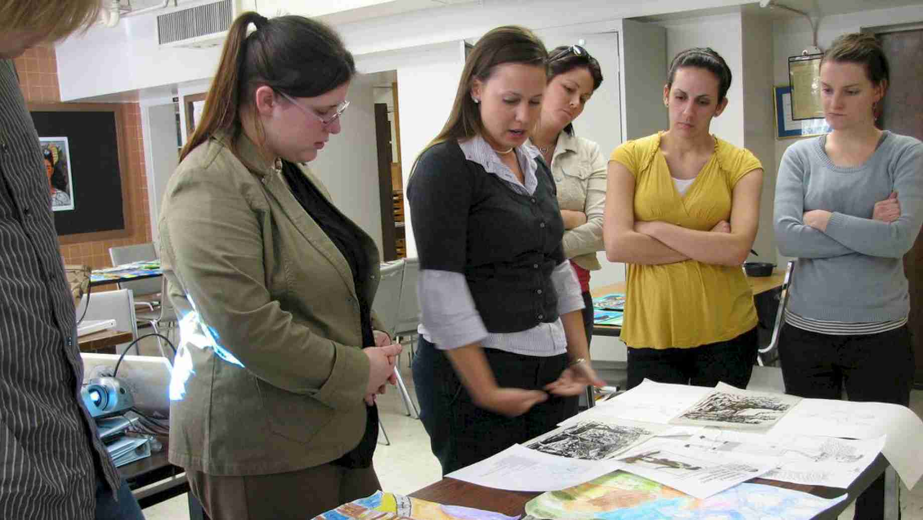 Art education student teachers meet to discuss student art from each of their internship school placements.