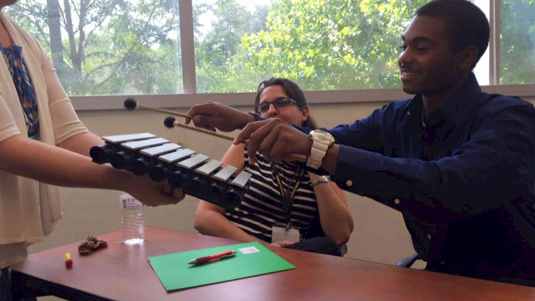 A musician-in-residence demonstrates simple instruments that they use in the hospital for bedside visits.