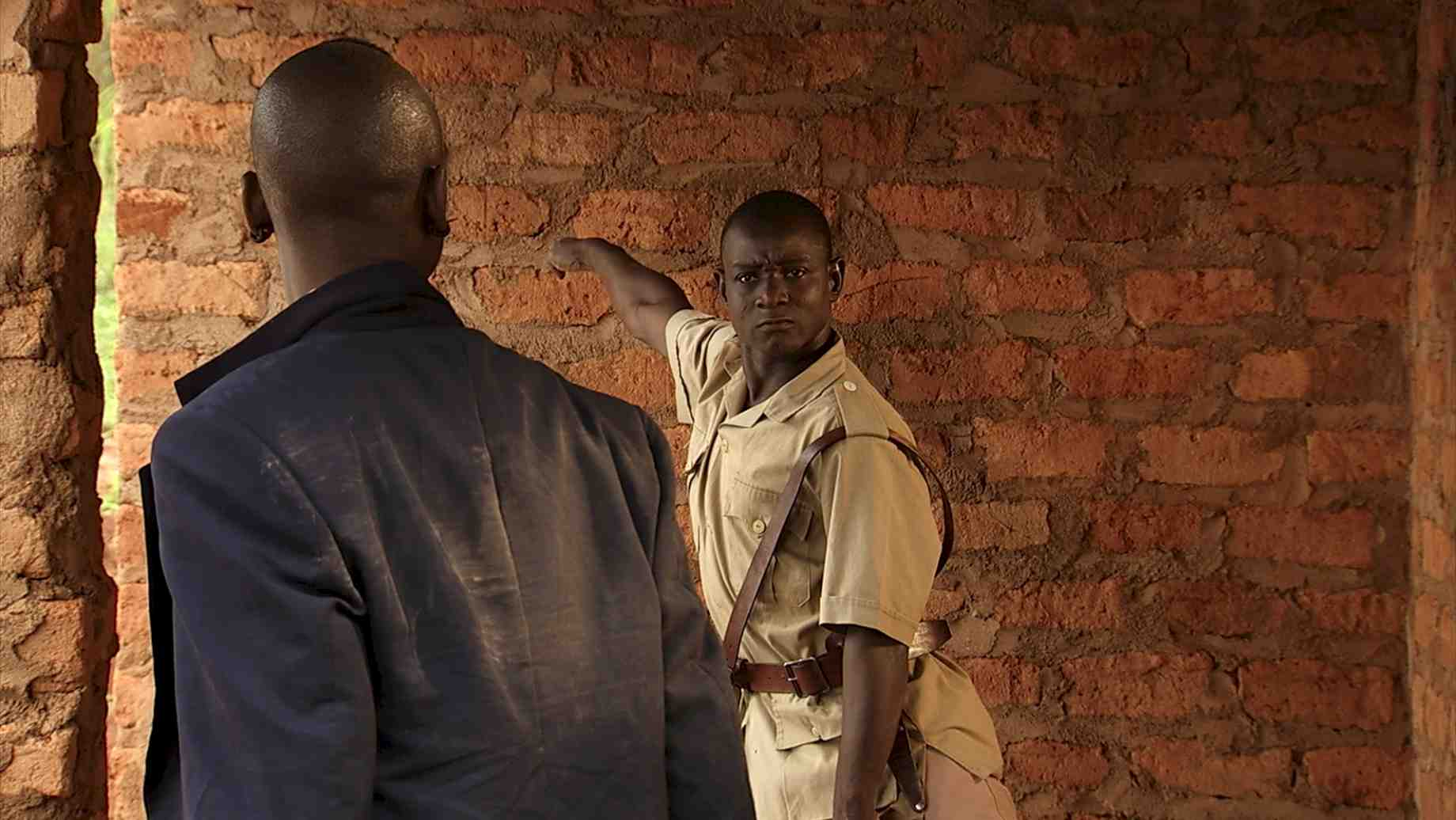 Souleymane Badolo, in NORA, as the policeman who attempts, but fails, to remove young Nora and her brother from their home.
