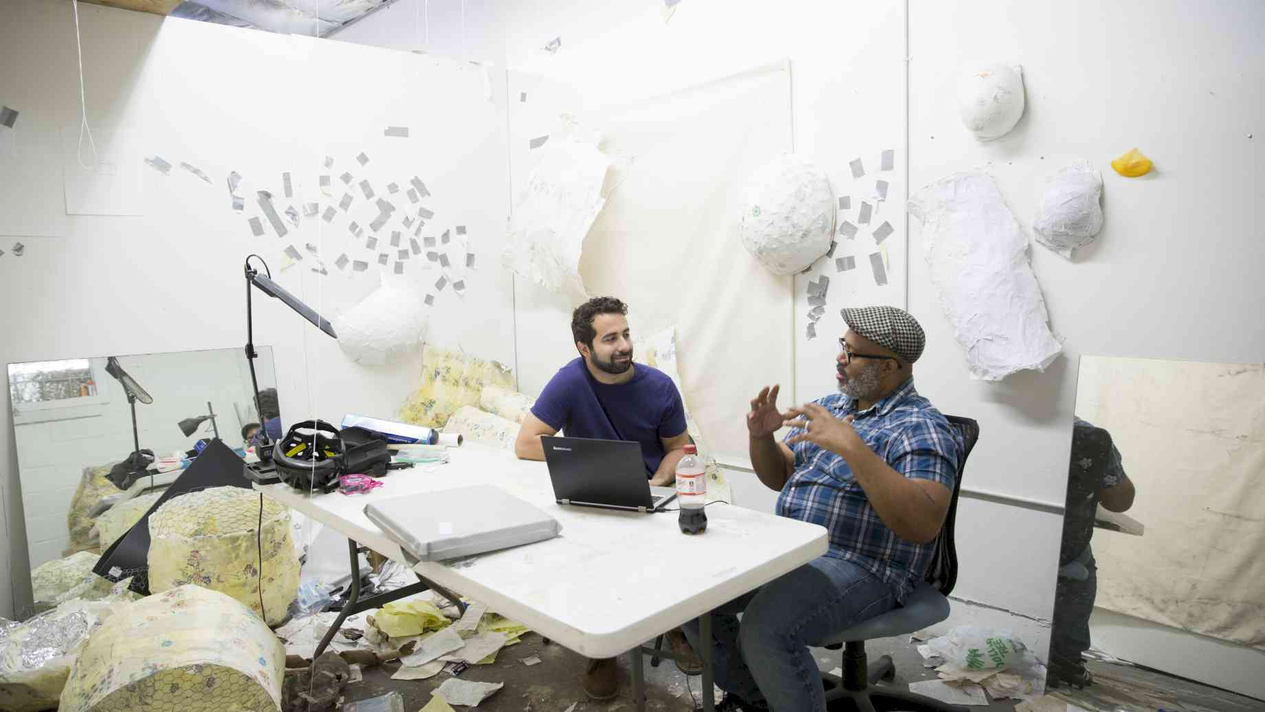 Visiting Artist Trent Doyle Hancock (right) conducts a studio visit with Art + Tech grad student Chris Bianchi